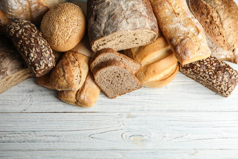 Different kinds of fresh bread on wooden table. Space for text. Different kinds of fresh bread on wooden table, flat lay. Space for text stock photos