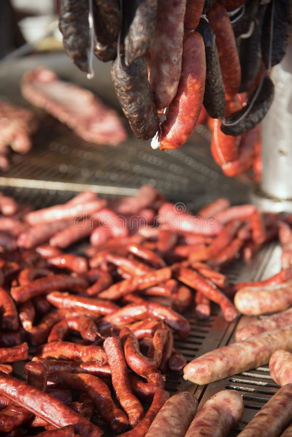 Different kinds of fresh spanish sausages hanging in bunches on the marketplace. Soft focus.6 stock image