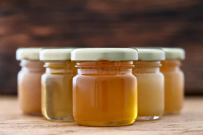 Different kinds of honey in a row. Jars with different kinds of honey in a row on a dark wooden background stock images