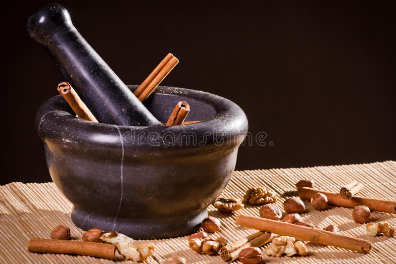 Different kinds of nuts in dark mortar royalty free stock image