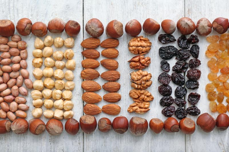 Different kinds of nuts and dried fruits on wooden background, top view stock images