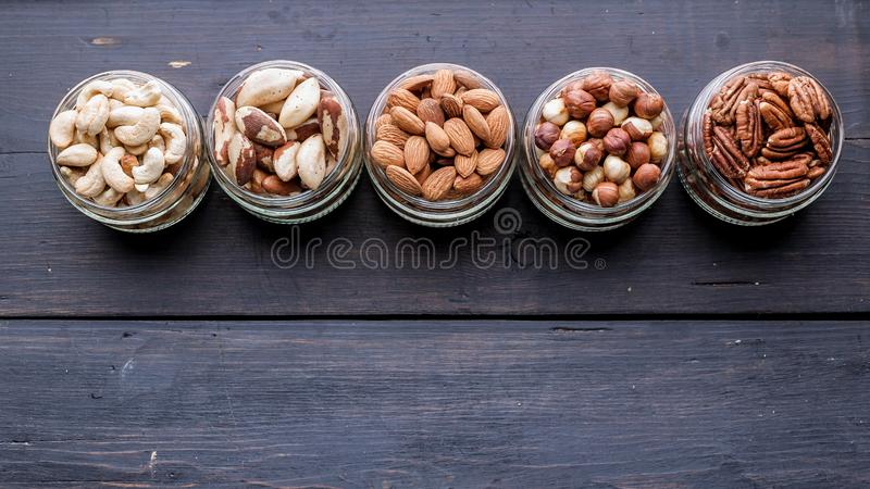 Different kinds of nuts in jars on a dark wooden background. Copy space royalty free stock image