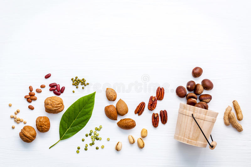 Different kinds of nuts . Walnuts,almonds ,pecan ,pea nuts, pistachio, pinto beans ,red kidney beans,soy beans and chestnut set u. P on white wooden background stock photos
