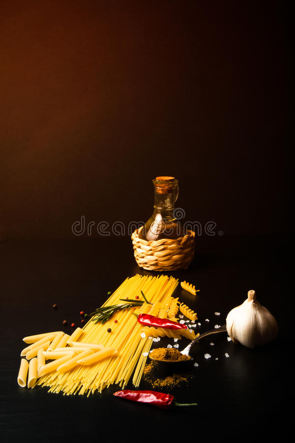 Different kinds of pasta, red chili pepper, rosemary, sea salt a. Nd spices on a black background. Selective focus. Toned stock image
