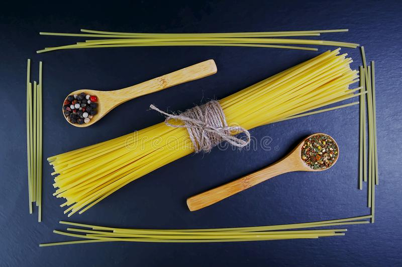 Different kinds of pasta spaghetti wooden spoons with spices background of food ingredients, image of the concept of advertising i royalty free stock photos