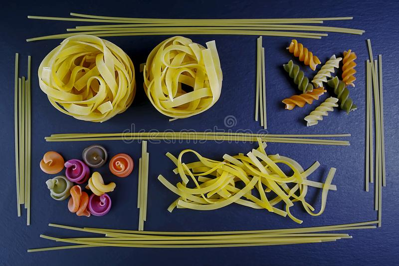 Different kinds of pasta tagliatelle, spaghetti, background of food ingredients, image of the concept of advertising in a restaura stock images