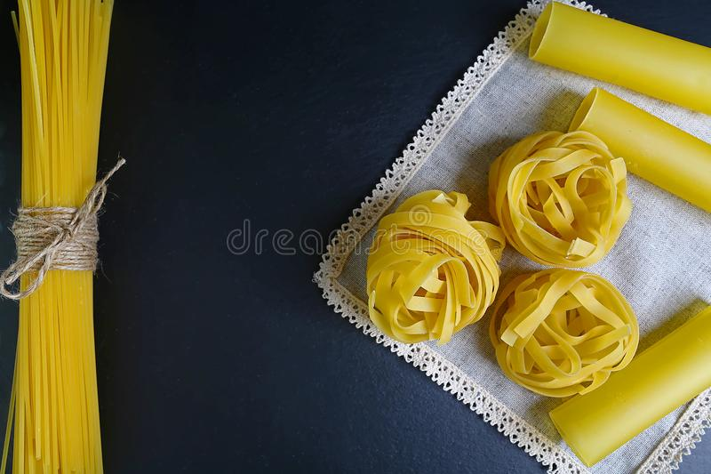 Different kinds of pasta tagliatelle, spaghetti, cannelloni on a napkin, background of food ingredients, image of the concept of a royalty free stock images