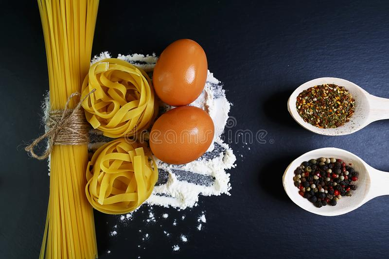 Different kinds of pasta tagliatelle, spaghetti, italian foods concept and menu design, spices on wooden spoons, raw eggs and flou stock image