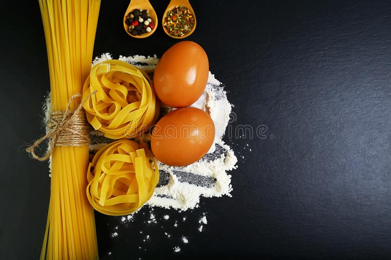 Different kinds of pasta tagliatelle, spaghetti, italian foods concept and menu design, spices on wooden spoons, raw eggs and flou royalty free stock images