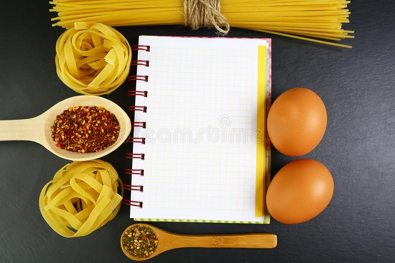 Different kinds of pasta tagliatelle, spaghetti, italian foods concept and menu design, spices on wooden spoons, raw eggs on a sha royalty free stock image