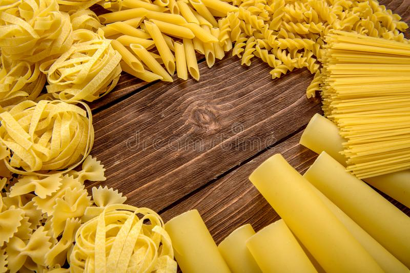 Different kinds of pasta on a wooden background. Farfalle, fettuccine, noodles, fusilli and penne rigate. stock photos