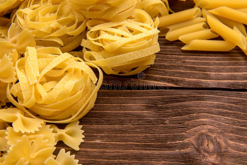Different kinds of pasta on a wooden background. Farfalle, fettuccine, noodles, fusilli and penne rigate. Tasty Italian cuisine royalty free stock photos