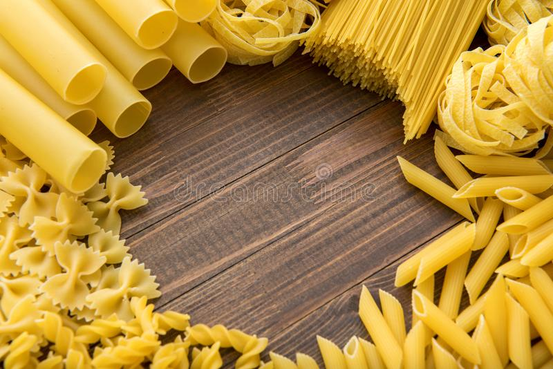 Different kinds of pasta on a wooden background. Farfalle, fettuccine, noodles, fusilli and penne rigate. Tasty Italian cuisine stock images