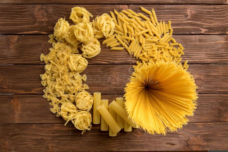Different kinds of pasta on a wooden background. Farfalle, fettuccine, noodles, fusilli and penne rigate. Tasty Italian cuisine royalty free stock image