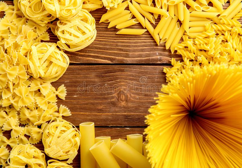 Different kinds of pasta on a wooden background. Farfalle, fettuccine, noodles, fusilli and penne rigate. Tasty Italian cuisine. stock photo