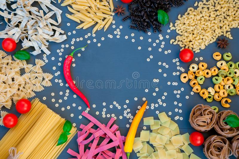 Different kinds of raw pasta on a blue background. Different kinds of raw pasta on a blue wooden background with spicy red pepper, tomatoes and other ingredients royalty free stock photos