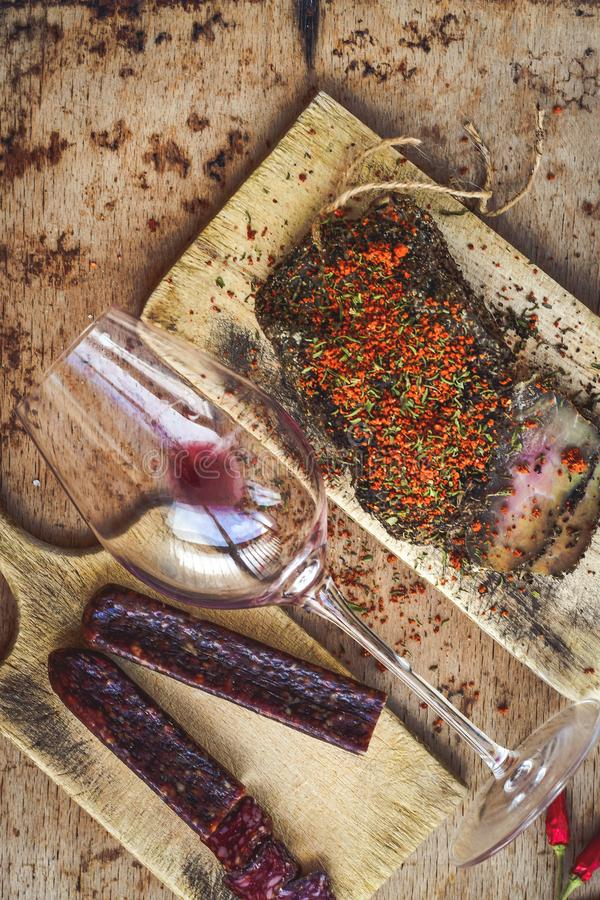 Salami and wine. Different kinds of Salami ,cold cuts,, empty glass for red wine peperoncino, fresh onion and spices as a rustic lunch stock photo