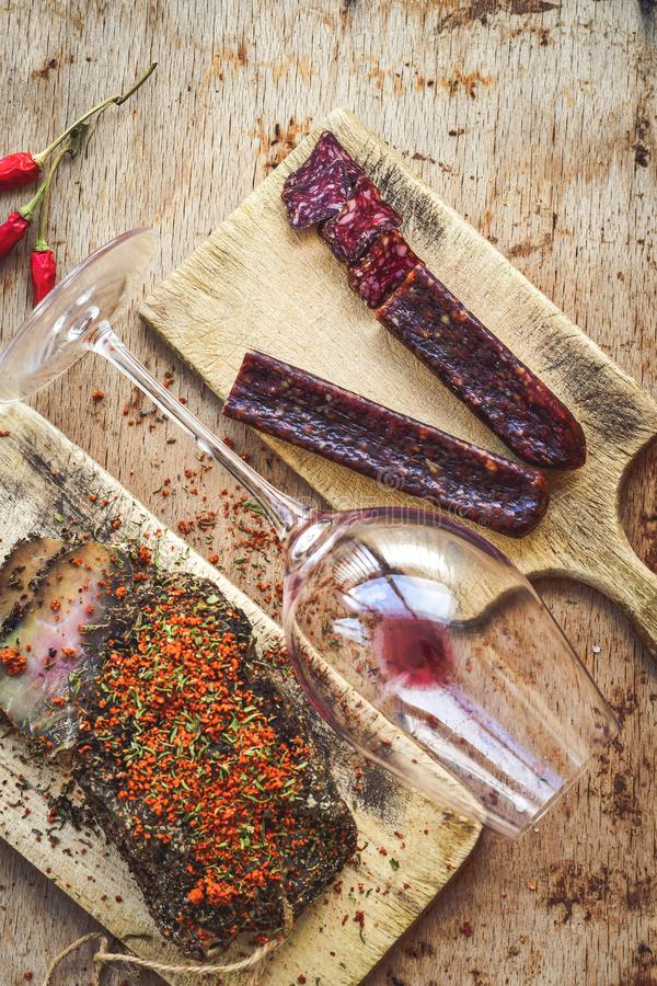 Salami and wine. Different kinds of Salami , empty glass for red wine peperoncino, fresh onion and spices as a rustic lunch stock image