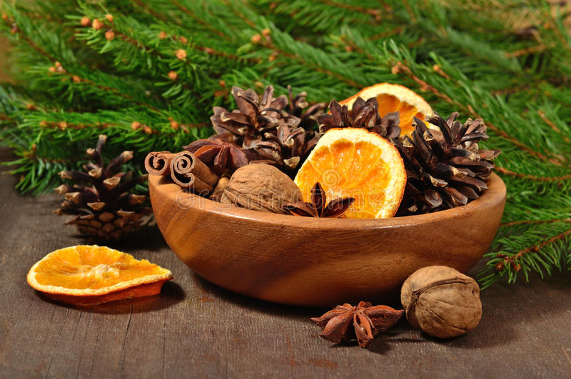 Different kinds of spices, nuts, dried oranges and cones in bowl stock photos