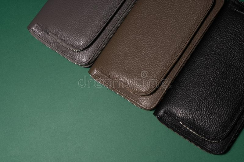 Different leather wallets on zipper. Green background. stock photo