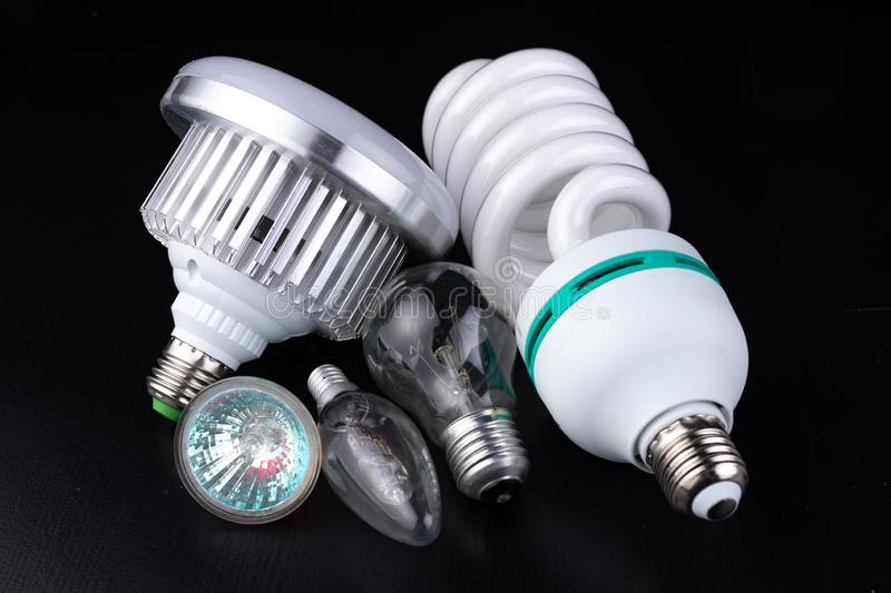 Different light bulbs and fluorescent lights on a wooden table. New types of lighting. Dark background stock photos