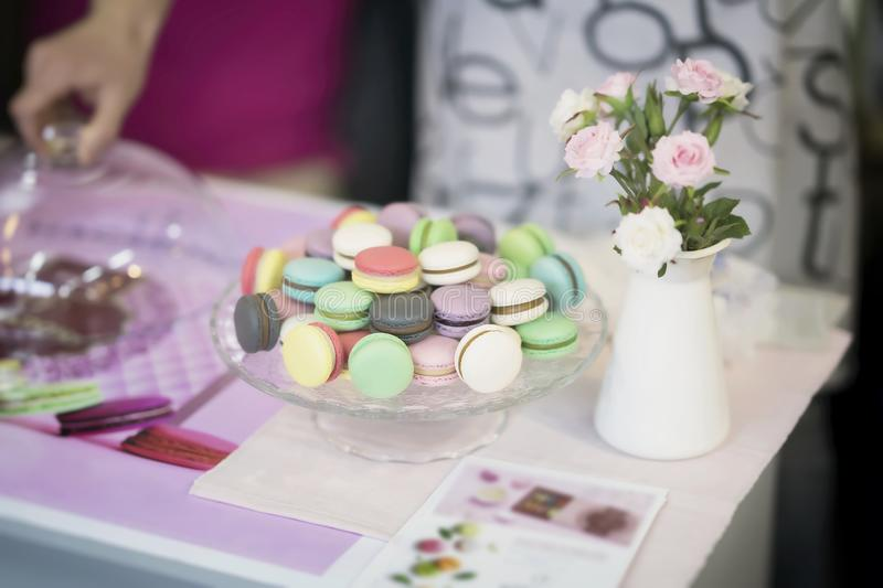 Different Macarons, spring flowers, roses, hand, tender pastel background. Romantic morning, gift, present for beloved royalty free stock photography