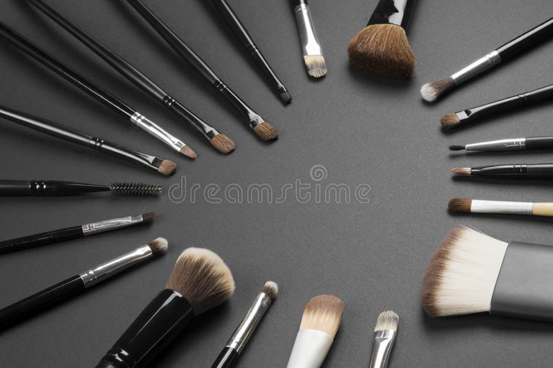 Different make-up brushes. Are in heart shape on gray background, loving make-up concept stock photography