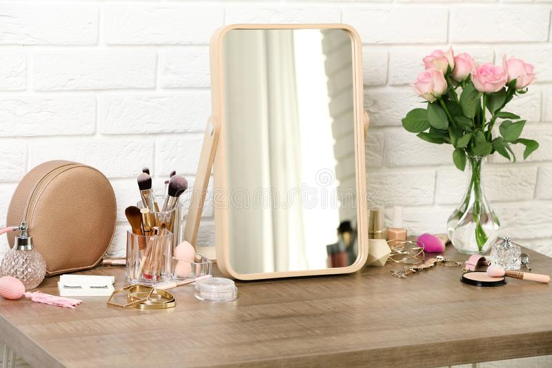 Different makeup products and accessories on dressing table stock images