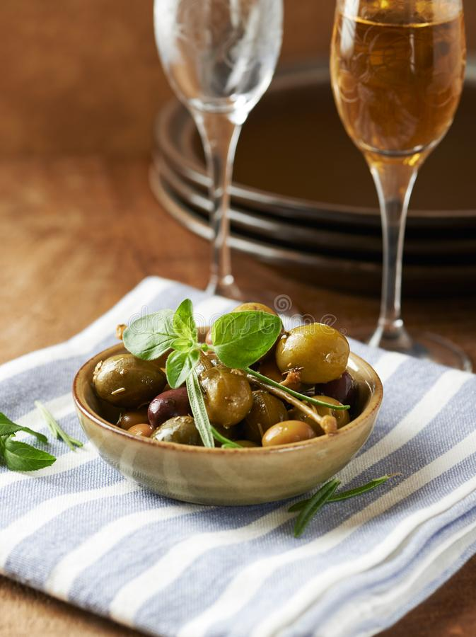 Different marinated olives and capers in a small ceramic bowl. Vertical royalty free stock photography