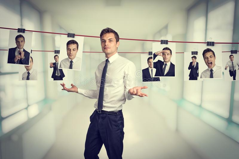A different me. Businessman with pictures hanging by a thread with different facial expressions royalty free stock photo