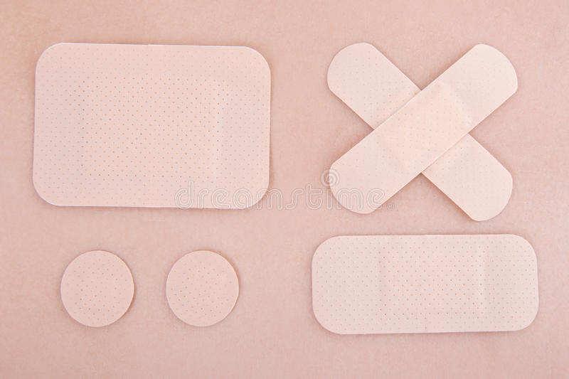 Different medical adhesive plasters on skin background royalty free stock photography