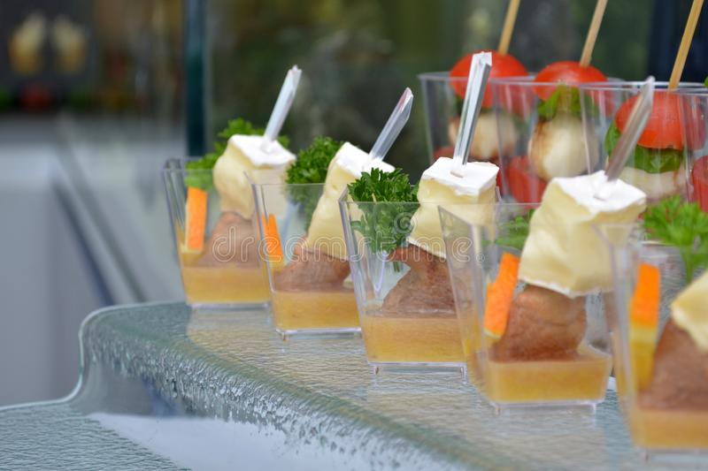 Different meet canapes in transparent glasses and wooden skewers on a glass step support on a banquet royalty free stock image
