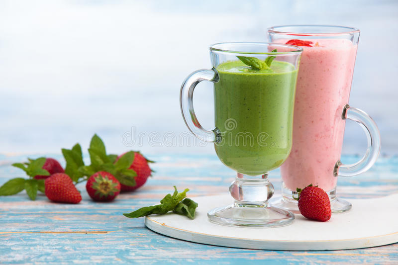 Different milkshakes on the table. Spinach and strawberry smoothie with mint leaves on wooden rustic table stock photos