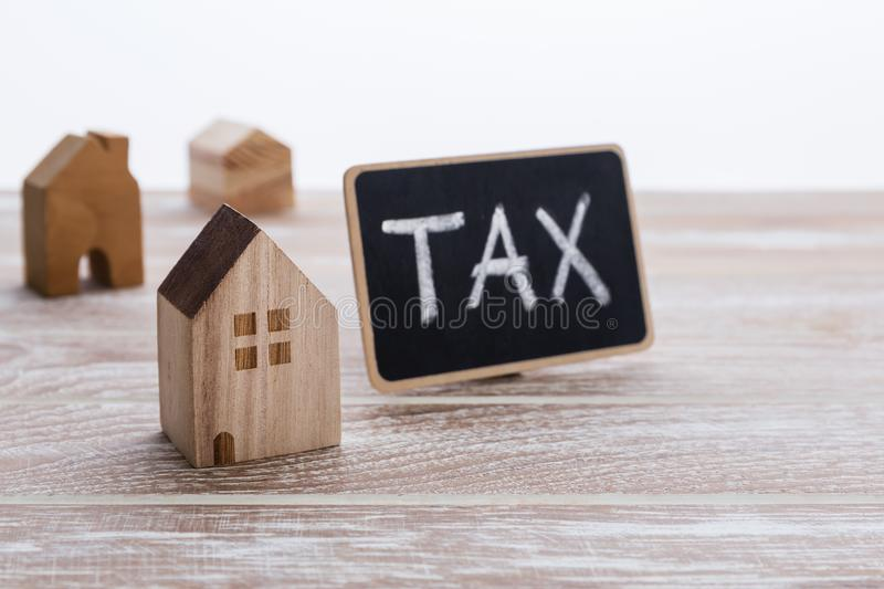 Different model of houses on wooden table with tax sign. For property tax concept royalty free stock photo