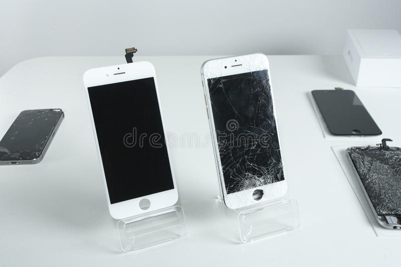 Different modern mobile phones with broken screen on white table stock photos