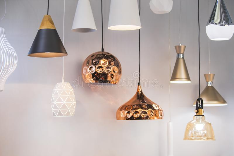 Different modern streamlined mirror copper chandeliers. Bubble metal copper shade pendant.  royalty free stock photo
