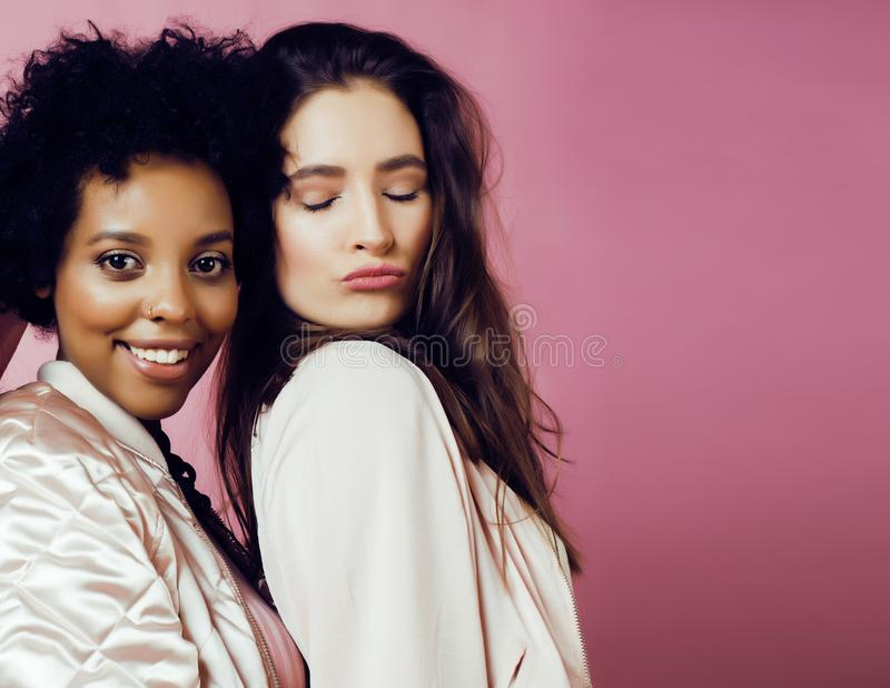 Different nation girls with diversuty in skin, hair. scandinavian, african american cheerful emotional posing on pink royalty free stock image