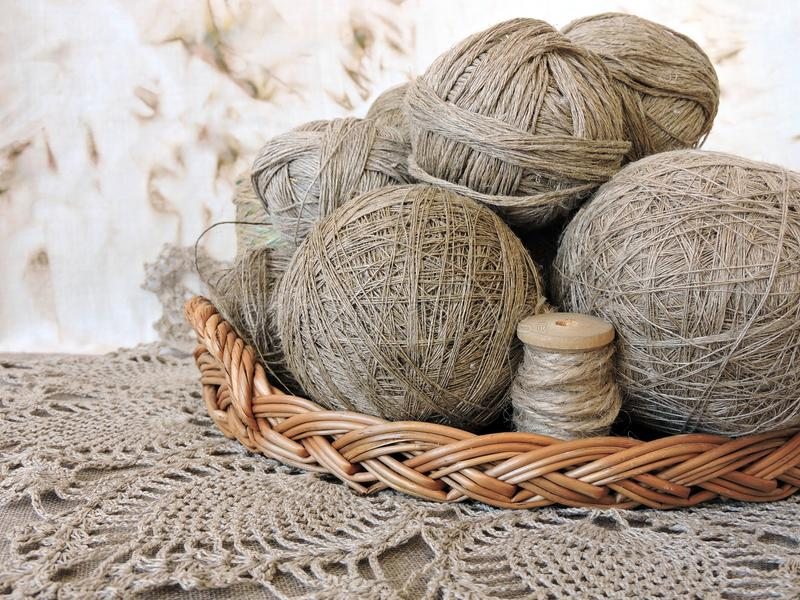Natural linen thread in wicker, Lithuania. Different natural linen yarn in balls in wicker on crocked surface stock photos