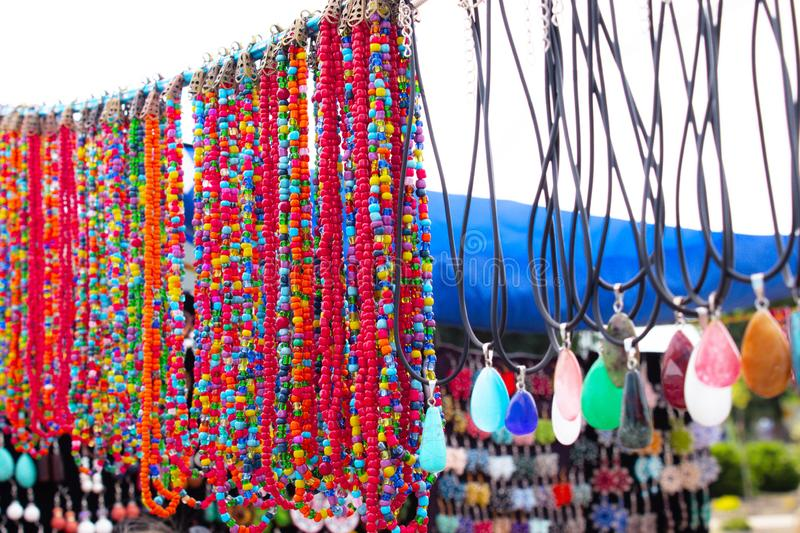 Different necklaces of various shapes and colors with colored stones on a blurred background stock image