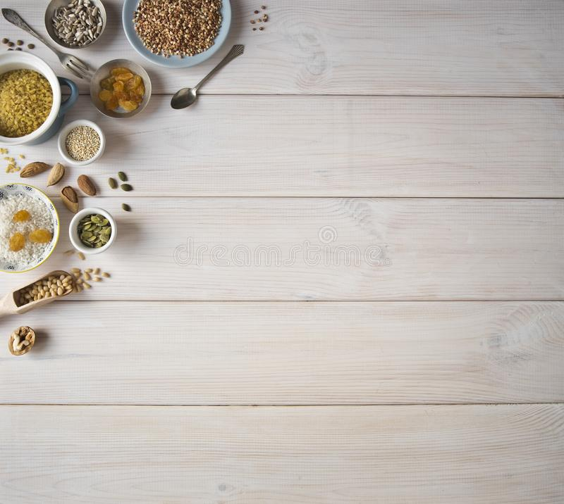 Different nuts, cereals, raisins on plates on a wooden table. Cedar, cashew, hazelnut, walnuts, almonds, pumpkin seeds, sunflower. Seeds, bulgur, buckwheat royalty free stock photo