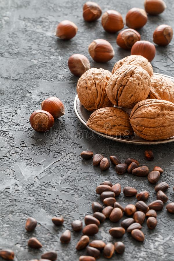Different nuts on dark stone table. hazelnut, walnuts, cedar. Many nuts are inshell and chistchenyh on table stock images