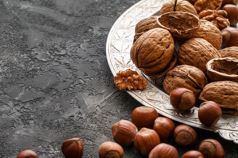 Different nuts on dark stone table. hazelnut, walnuts. Many nuts are inshell and chistchenyh on table royalty free stock photos
