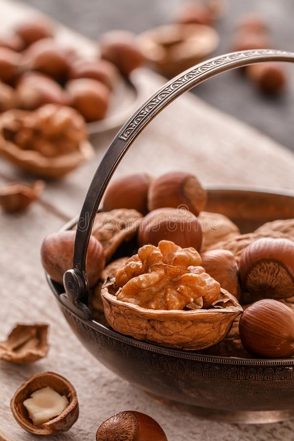 Different nuts on dark stone table. hazelnut, walnuts. Different nuts on dark stone table. hazelnut, walnuts, many nuts are inshell and chistchenyh on table royalty free stock photography