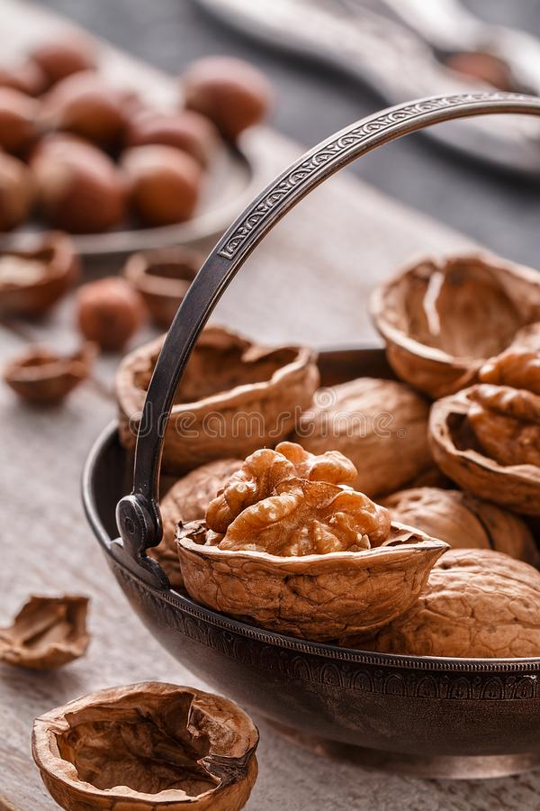 Different nuts on rustic table. hazelnut, walnuts. Many nuts are inshell and chistchenyh on table stock image