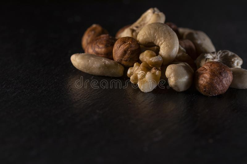 different nuts on a slate plate stock photography