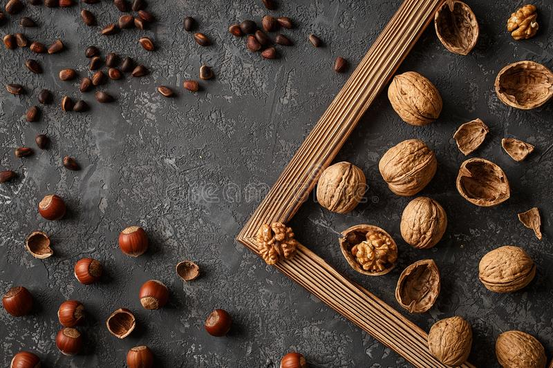 Different nuts on stone table. Cedar, hazelnut, walnuts. Many nuts are inshell and chistchenyh on stone table stock images