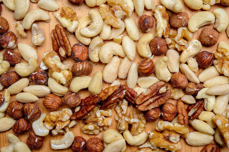 Different nuts on wooden ground. From above stock photography