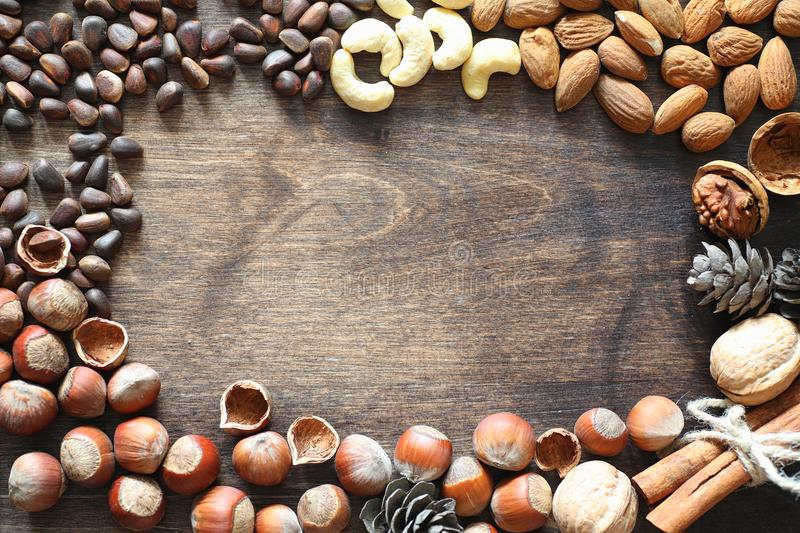Different nuts on a wooden table. Cedar, cashew, hazelnut, walnu. Ts and a spoon on the table. Many nuts are inshell and chistchenyh on a wooden backgroundr stock photos