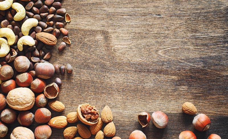Different nuts on a wooden table. Cedar, cashew, hazelnut, walnu. Ts and a spoon on the table. Many nuts are inshell and chistchenyh on a wooden backgroundr royalty free stock photography