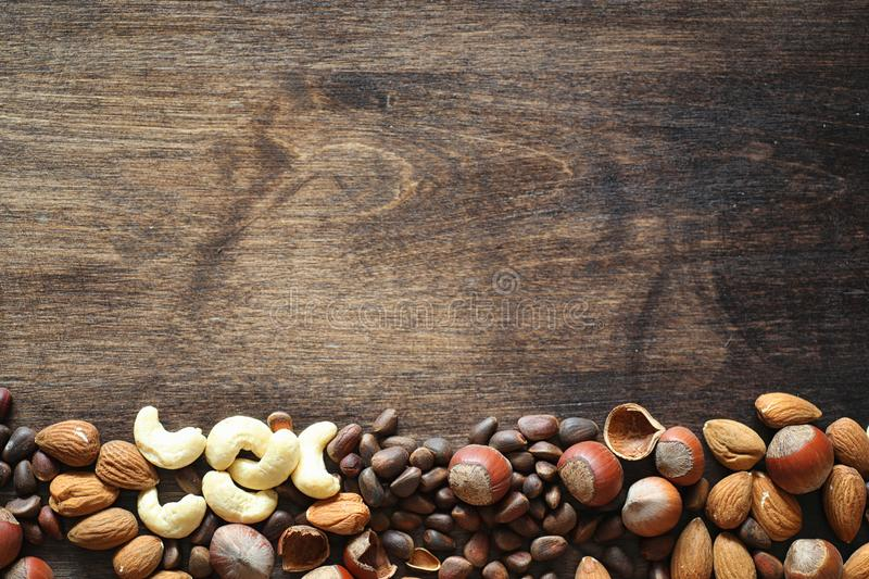 Different nuts on a wooden table. Cedar, cashew, hazelnut, walnu. Ts and a spoon on the table. Many nuts are inshell and chistchenyh on a wooden backgroundr royalty free stock image